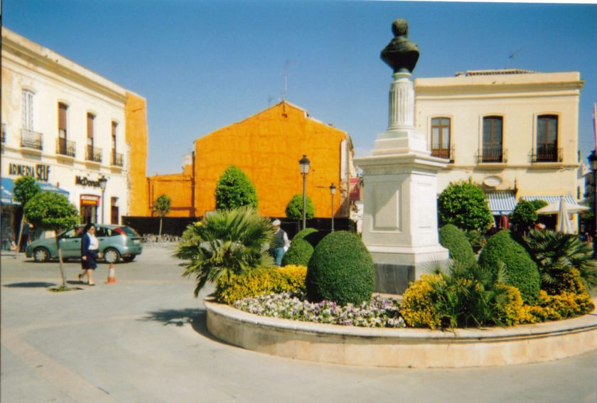 A circular flowerbed in the town in Ronda with greenery and other plants. In the centre is a tall white pedestal with a bronze bust of someone's head and shoulders on the top.