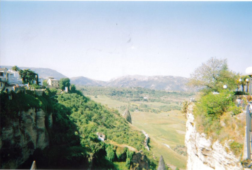 Scenic view of a green valley in Ronda, with a few buildings high up on hills to the side.
