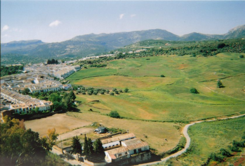 Another scenic view of Ronda, with a wide expanse of green on the right, and terraced buildings in the town on the left.