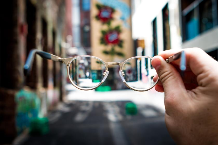 A pair of glasses being held up in front of a blurry street scene