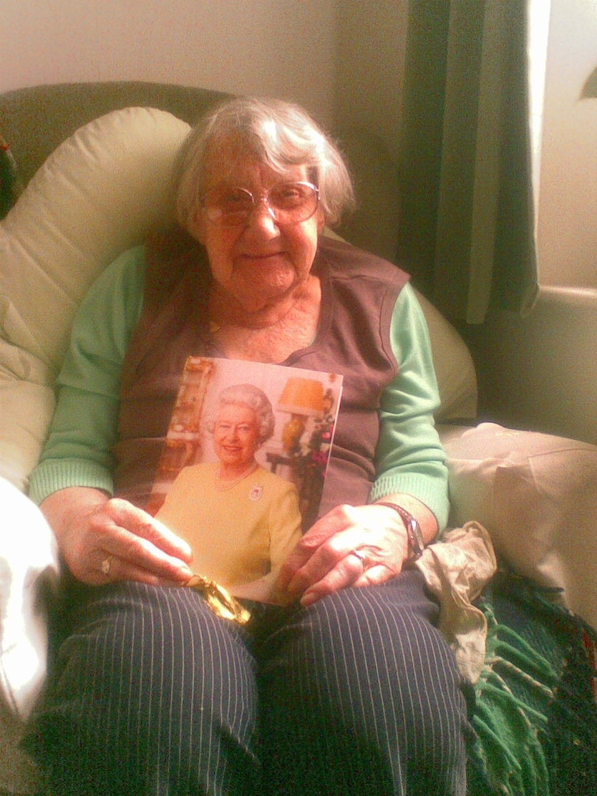 My Nan smiling, as she sits in her armchair holding her 100th birthday card from the Queen