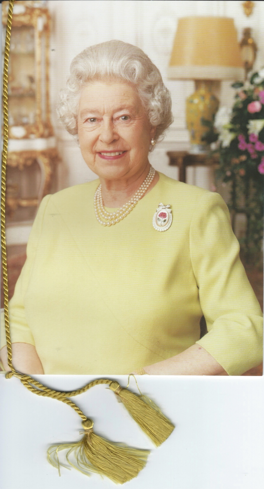 The front of the Queen's 100th birthday card to my Nan, showing Her Majesty smiling while wearing a light green top with a white brooch and a necklace with 3 rows of beads. A soft gold tassel hangs from the top left corner of the card.