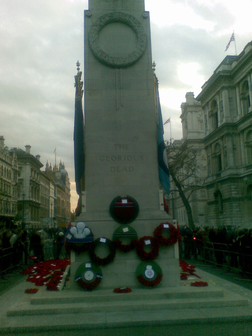 The tall stone Cenotaph monument in London, with wreaths of poppies around the base.