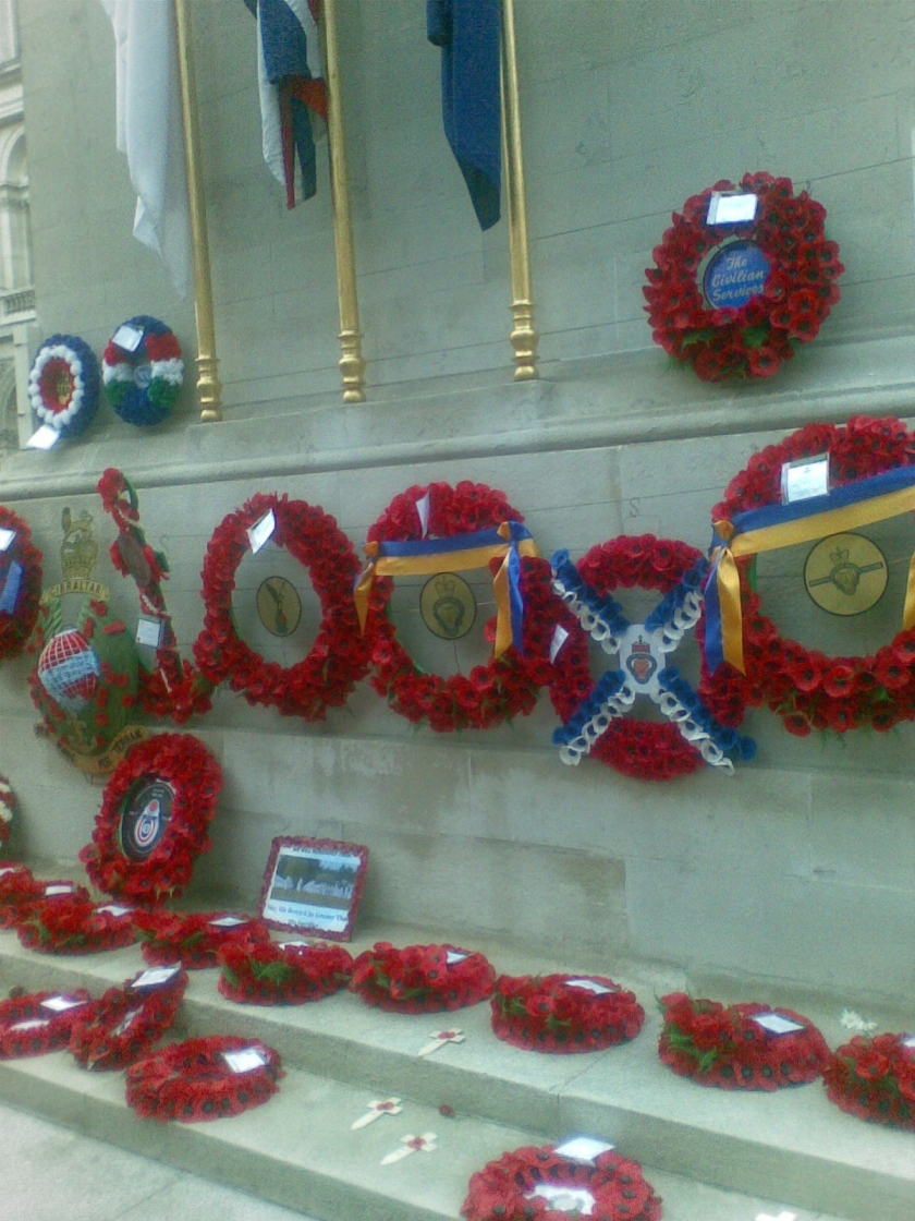 Poppy wreaths at the base of the Cenotaph monument, some adorned with colourful ribbons