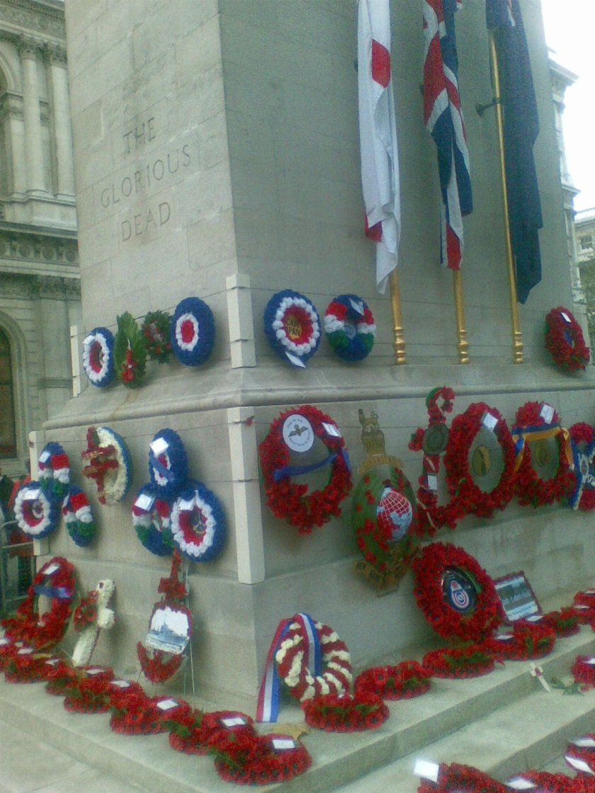 Poppy wreaths at the base of the Cenotaph monument, with 3 flags including the Union Jack hanging just above them.
