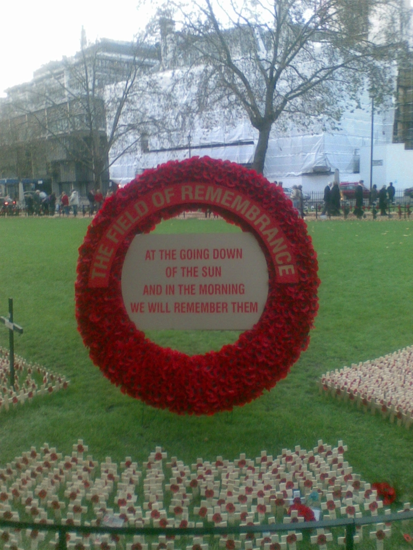 Large poppy wreath sign in front of a large grassy area. Text arching around the top reads The Field of Remembrance. A plaque in the centre of the wreath reads at the going down of the sun, and in the morning, we will remember them.