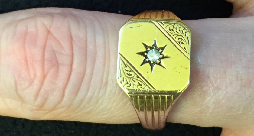 Gold signet ring, in a square shape with rounded corners, with the top right and bottom left corners having an ornate wavy design. An 8-point star in the centre of the ring holds a small diamond.