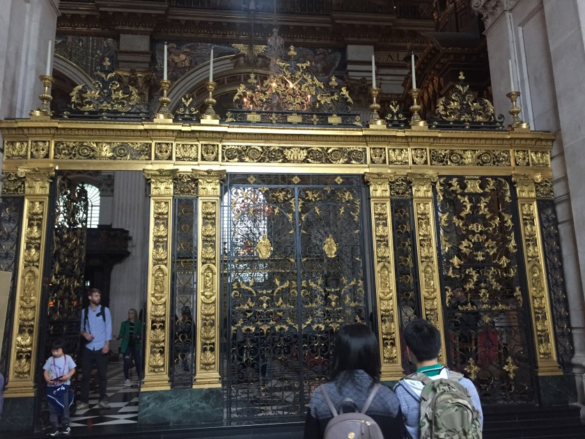 Large black and gold gate with a very ornate design inside St Paul's Cathedral