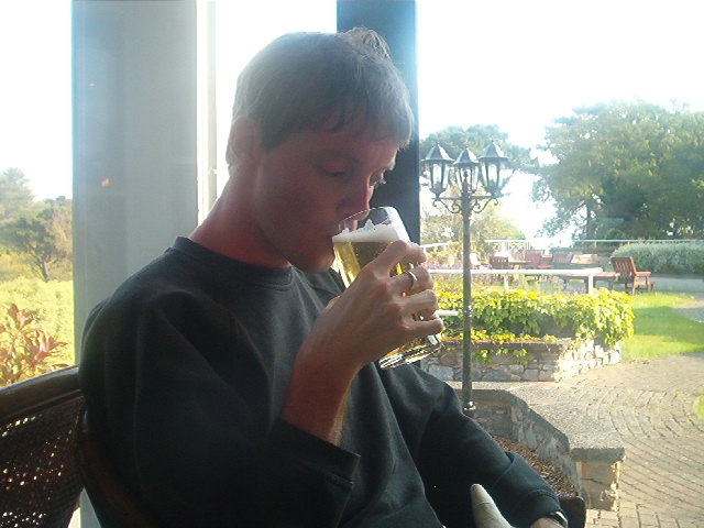 Glen sitting by a window and drinking a pint of cider. The grass, trees, tables and chairs outside the window are bathed in sunshine.