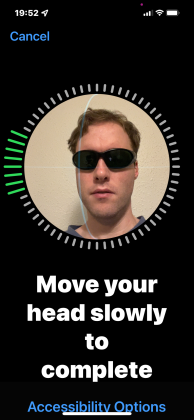 iPhone 13 screenshot. My face with sunglasses on is positioned inside a circular frame. All around the frame are small grey bars, which turn into longer green bars as I turn my head to help the phone recognise me. Large text below the frame says Move your head slowly to complete, along with a link for accessibility options.