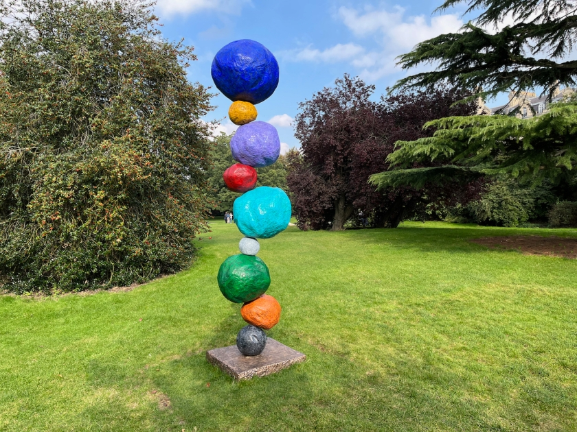 Tall sculpture made of different coloured boulders, unevenly stacked on top of each other in alternating small and large sizes. Colours include blue, green, organge and red. The sculpture is standing on a square panel on the grass, with trees in the background and wispy clouds in the blue sky above.
