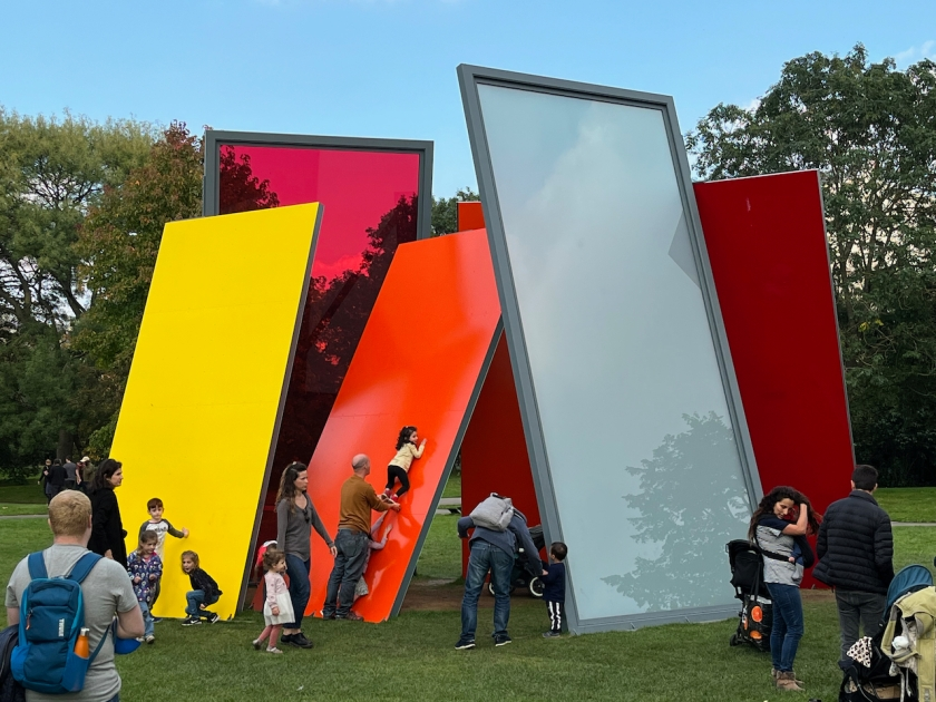 An art installation of very tall and wide glass panels in different colours, including yellow, orange and red, all sloping inwards as if resting against each other for support. Families are gathered around it with children taking an interest. One father is sliding his daughter up one of the panels with his hands under her feet.